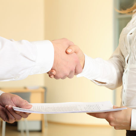 Man and woman shaking hands in office and giving papers